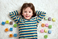 Cute child, boy, play with toy blocks, lying on the floor Royalty Free Stock Photo