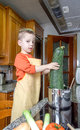 Cute child chef cooking big zucchini in a pot with apron and other vegetables on the kitchen Royalty Free Stock Images