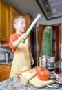 Cute child chef cooking big zucchini in a pot with apron and other vegetables on the kitchen Royalty Free Stock Image