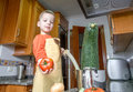 Cute child chef cooking big zucchini in a pot with apron and other vegetables on the kitchen Stock Photography