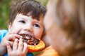 Cute child eating cocoa snail outdoors Royalty Free Stock Photos