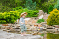 Cute child fishing by the pond in the beautiful garden Stock Image