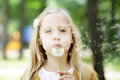 Cute child girl blowing dandelion Royalty Free Stock Photo
