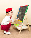 Cute child girl drawing chalk on easel in suit of artist  in kindergarten Royalty Free Stock Photo