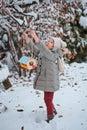 Cute child girl hangs bird feeder in winter snowy garden on teh tree Royalty Free Stock Image