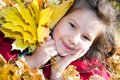 Cute child girl playing with fallen leaves in autumn park Stock Photo