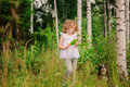 Cute child girl playing with leaves in summer forest with her dog. Nature exploration with kids.