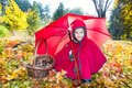 Cute child girl playing with umbrella in leaves in autumn park Stock Photography