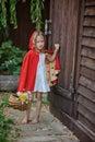 Cute child girl plays little red riding hood in summer garden