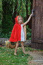 Cute child girl plays little red riding hood in summer garden cape opens the door while playing Royalty Free Stock Photos
