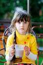 Cute child girl sitting with a cup of tea outdoors Stock Photo