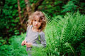 Cute child girl on the walk in summer woods with ferns Royalty Free Stock Photo