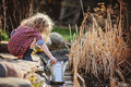 Cute child girl with watering can gathering water from pond in plaid dress in spring sunny garden Stock Photos