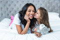 Cute child kissing her mother on the bed Royalty Free Stock Photo