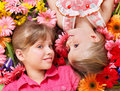 Cute child lying head to head on the flower. Royalty Free Stock Image