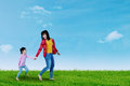 Cute child and mother walking on meadow Royalty Free Stock Photo