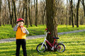 Cute child out cycling drinking bottled water little boy with his bike in a wooded park standing with his bicycle propped up Stock Photo