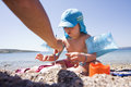 Cute child painting the stones at the beach caucasian laughing and playing with many coloured plastic toys and Royalty Free Stock Image