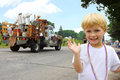 Cute child at parade a smiling little boy is waving as he watches floats go by in an american on a summer day Royalty Free Stock Photography