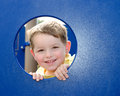 Cute child peeks through hole at playground Royalty Free Stock Photo