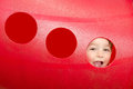Cute child peeks through hole at playground Royalty Free Stock Photos