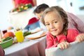 Cute child portrait of happy girl sitting at festive table and looking at camera Stock Images