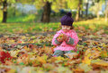 Cute child sitting on autumn bright colorful foliage and holding apple Stock Photography