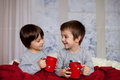 Cute children, boys, sitting in a big chair in pajamas, drinking Royalty Free Stock Photo
