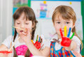 Cute children painting at kindergarten preschool with their palms Stock Photography