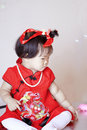Cute Chinese little baby in red cheongsam play soap bubbles