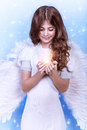 Cute christmas angel on blue snowy background adorable girl with candle in hands religious winter holiday peace and harmony Royalty Free Stock Photo