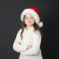 Cute christmas girl young wearing a white wooly sweater and a red santa hat Royalty Free Stock Photos