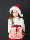Cute christmas girl young wearing a white wooly sweater and a red santa hat Stock Photography