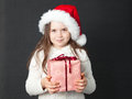 Cute christmas girl young wearing a white wooly sweater and a red santa hat Stock Photos