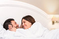 Cute couple in bathrobe showing affection close up portrait of young laying together on bed hotel room girl Royalty Free Stock Images