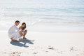 Cute couple drawing a heart in the sand at beach Stock Photo