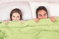 Cute couple lying in bed under the covers smiling Royalty Free Stock Image