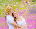 Cute couple photographing of themself cheerful make photo outdoors on beautiful pink floral meadow in summer garden affection and Stock Photo