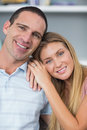 Cute couple sitting on the couch smiling at camera in room home Royalty Free Stock Images