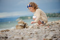 Cute curly child girl building stone tower on summer sea side Royalty Free Stock Photo