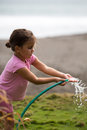 Cute curly girl watering flowers in the garden matapalo costa rica may with pacific background costa rica Stock Image