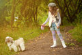 Cute curly haired girl walking with dog in park image of Royalty Free Stock Image