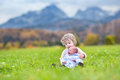 Cute curly toddler girl and her newborn baby brother playing in a field with snow covered mountains the background Royalty Free Stock Photography