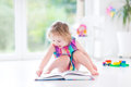 Cute curly toddler girl reading a book Royalty Free Stock Photo