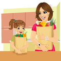 Cute daughter helps her mother to carry groceries paper bags in kitchen