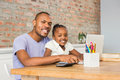 Cute daughter using laptop at desk with father in living room Stock Image