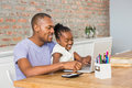 Cute daughter using laptop at desk with father in living room Royalty Free Stock Image