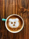 Cute dog face latte art coffee in white cup on wooden table