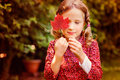 Cute dreamy child girl hiding behind red autumn leaf in the garden Royalty Free Stock Photo