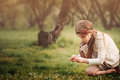 Cute dreamy kid girl in beige outfit picking flowers in spring garden Royalty Free Stock Photo